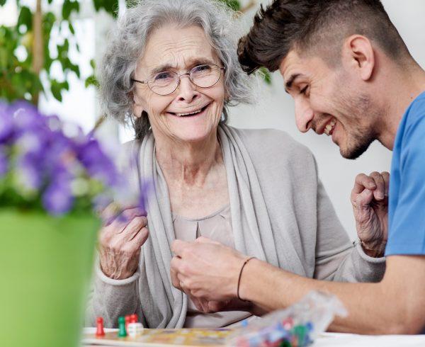 Seniorin spielt mit Pflegepersonal ein Brettspiel