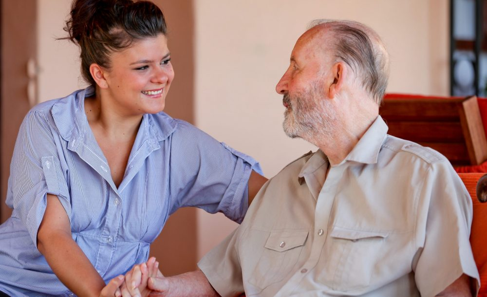 elderly man with nurse carer or granddaughter.