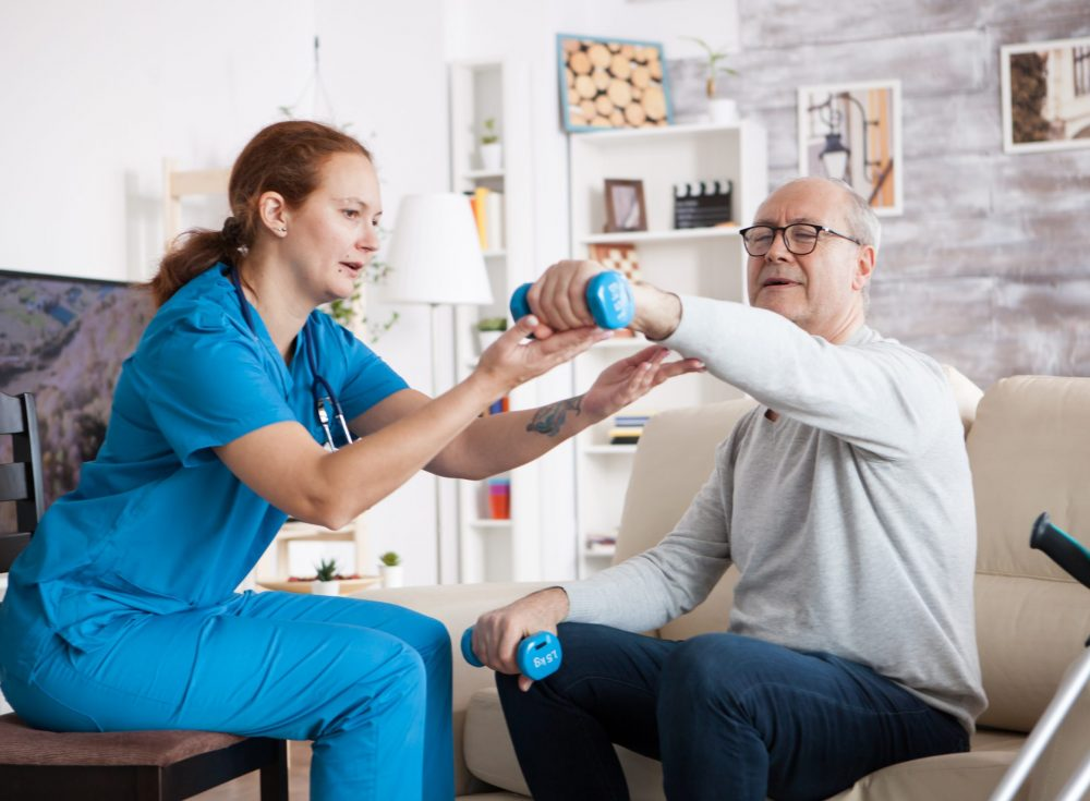 Senior man in nursing home with doing physical therapy with help from nurse using dumbbells.