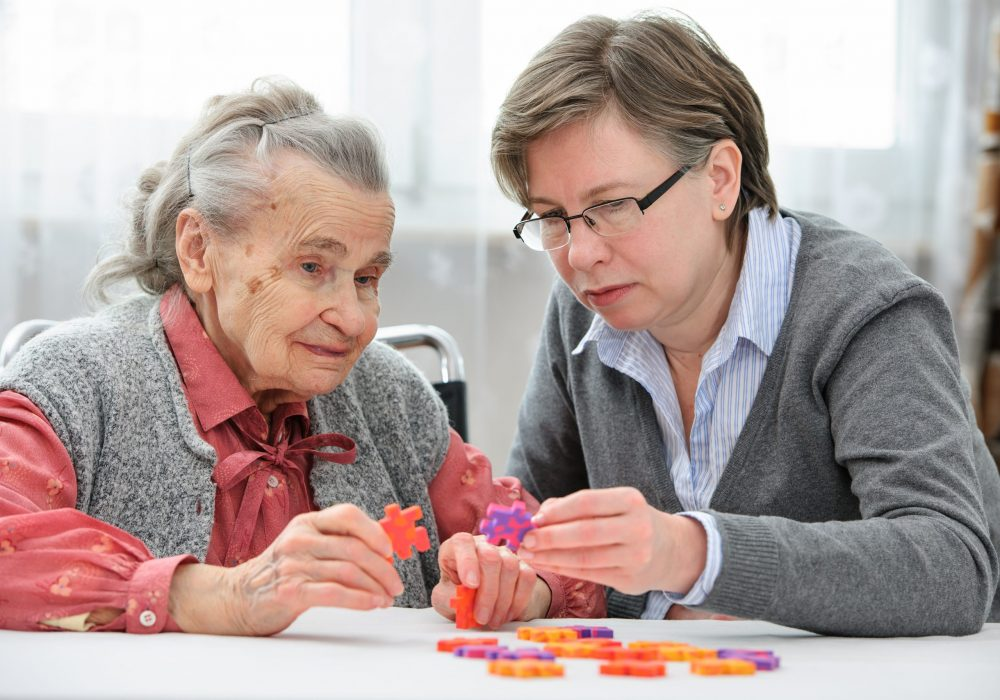 Elder care nurse playing jigsaw puzzle with senior woman in nursing home